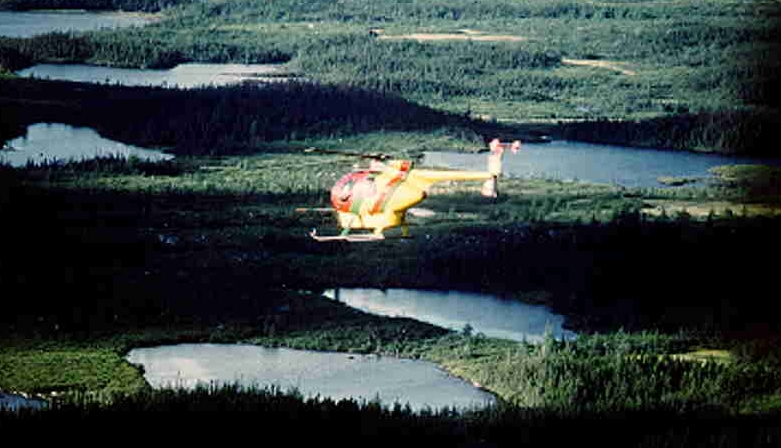 Southern Longe Range Mountains, SW Newfoundland. Hughes 500-D helicopter of Viking Helicopters flying above the boggy and partially wooded highlands, photo taken from another helicopter.